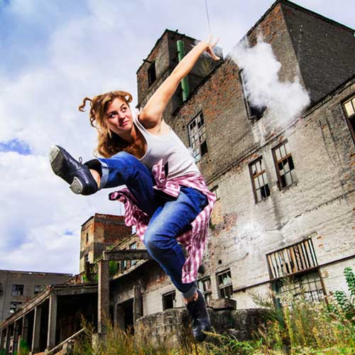 tap dancer jumping in front of old building